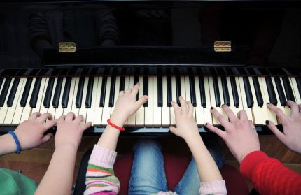 kids-many-hands-on-piano